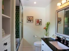 This contemporary bathroom from HGTV features a larger vanity and custom built-in storage behind the shower tub combo.
