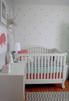 Mostly white nursery with pink, aqua, and silver accents. I love the polka dot wall!