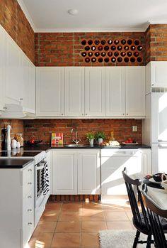 Miejsce na wino wygospodarowane nad szafkami kuchennymi, w ścianie w surowej cegły? Czemu nie ...