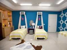 This youthful bedroom is a vibrant blue with charming decor – including pink faux animal heads mounted above the twin beds. Striped bedding and a lattice-inspired overlay on the wall add a graphic punch to the eclectic room.