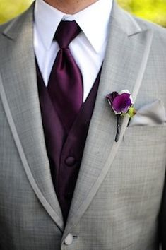 Grey jacket, purple vest, purple tie, and a purple boutonnière make this a classic and stylist wedding suit.