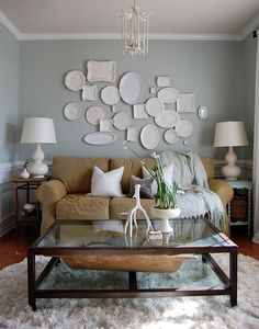 Display the a group of monotone plates, in an assortment of shapes and sizes, for an architectural appeal.