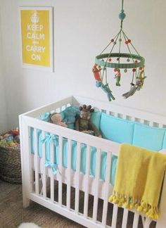 Modern yellow & turquoise blue gender neutral nursery design with white modern crib, turquoise, blue crib bedding, yellow tassle, throw, turquoise blue & green Big Jungle mobile, jute rug and yellow keep calm & carry on print.