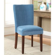 This set of two teal velvet parson dining chairs are constructed on a mid-tone brown, solid wood frame complemented by rich teal, velvet fabric that will add a pop of color to your home.