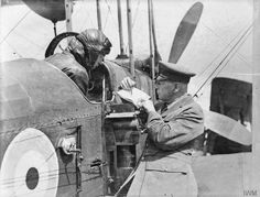 MINISTRY OF INFORMATION FIRST WORLD WAR OFFICIAL COLLECTION. The officer of an R. A. F, Mobile photographic Section showing to a Pilot of a B.E. 12, the areas to be photographed on a map which is resting on a probable L type camera.