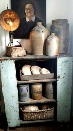 Early Stoneware ~ Great crock collection in a primitive cupboard creates a rustic country design.