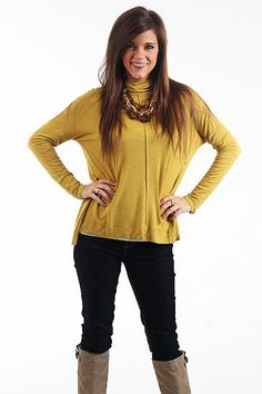 """Easy Does It Top, Mustard $36.00  We love this little turtleneck! The vibrant mustard color is a great backdrop for this simple top, made of a super soft material with a seam down the front, dolman sleeves and a slightly longer hem in the back. It's a great piece to layer under sweaters and cardigans this fall and winter!   Fits true to size. Miranda is wearing a small.   From shoulder to hem:  Small - 23""""  Medium - 24""""  Large - 25"""""""
