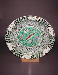 Fitzwilliam Museum Collections (Id:74522)... dish Islamic pottery; category Iznik; c. 1585 —1599 painted in red slip, black, blue, green and black under a colourless glaze Shape: segmental bowl with a flange rim, sits on a low, wide foot ring height, whole, 7.3, cm width, whole, 37.4, cm diameter, rim, 37.4, cm diameter, base, 21.8, cm weight, whole, 1982, g