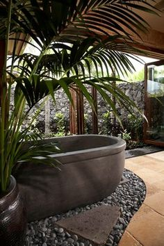 This Hawaiian home takes nature to the interior by highlighting custom items like concrete bathtubs and sinks. The large, pocket doors create the walls to this home--walls that can be added and removed as desired. This Kukio home rests on the sunny side of the Big Island and serves as a perfect example of our style, blending the outdoors with the inside of a home.