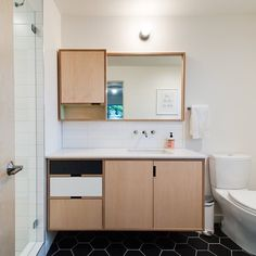 Simple and elegant plywood bathroom vanity, with a built-in mirror and cabinet above. And look at that black octagonal tile! Designed by Kerf. Check out our instagram by clicking on the visit button, or @kerfdesign.