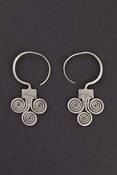 The spiral of these earrings reminds of the snake image, that represents fertility of the earth.This symbol is often represented in ornaments of rural communities in all of Asia.        Origin: Guizhou, China      Age: First half 1900      Material