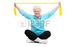senior gymnastique: senior femme faisant des exercices avec une bande de résistance