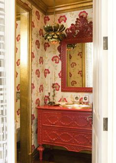Red and gold powder room with floral wallpaper designed by Erinn Valencich