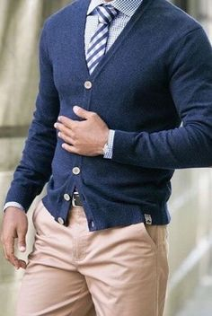 Navy blue cardigan, blue stripe neck tie, check shirt and pale brown chinos