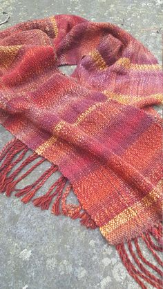 This Saori style hand woven scarf is a mix of hand spun yarns and mill made yarns and is one of a kind. When I decide to create a new piece I first go to my handspun shelf and choose colors that go well together. I mix and match these yarns as I weave to create an original piece.  This scarf measures 75 inches long and is 12 inches wide with 4 inch long braided fringe.  The hand spun yarn was created by me and includes Merino and Falkland wool and silk. This is the perfect neck warmer for…