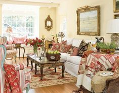 A Montecito cottage living room that includes not only reds, but also turquoise blue and mustard yellow French bergères, and an 18th-century French coffee table, make it true French-country style.