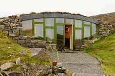 Hebridean Earth House - beautiful front view with staggered windows and piled stone facing