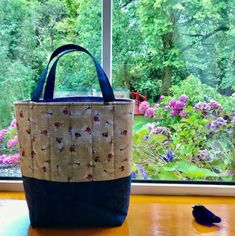Oh-la-la! Say 'oui, oui' to this lovely tote with these dapper-looking dogs dressed in a French style. The fabric on the top half of the bag shows a mix of dogs dressed in striped tops, neckerchiefs and berets on a beige printed background. This is paired with a dark blue denim-look fabric on the bottom and on the handles. The lining fabric is a lovely blue and white floral. Disney Tote Bags, Dog Tote Bag, Quilted Tote Bags, Cat Bag, Cotton Quilting Fabric, Neckerchiefs, Dog Dresses, Lining Fabric, Blue And White