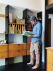 In his Portland home, Ty Milford peruses a book near the George Nelson–inspired built-ins fabricated by Big Branch Woodworking.    This originally appeared in Midcentury Renovation in Portland Capitalizes on Nature with Seven Doors to the Outside.