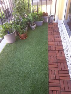 Balcony with artificial grass, decking and plants.