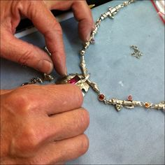"""Micky Roof working on a """"Finger Lakes"""" themed ensemble with (mostly) customer's gems - give or take a pink tourmaline - finished piece can be seen here: http://www.ithacajewelbox.com/images/stories/hdav-neck-1-tile.jpg"""