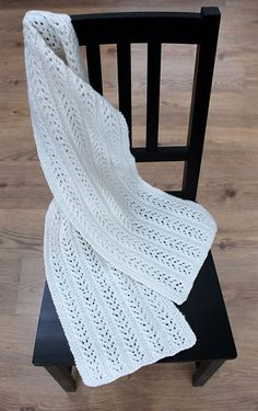 A simple lacy scarf with five panels of branching pattern repeats and a moss stitch edging border.