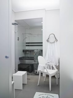 Käytävän varrelta ja alkovista saatiin tilaa uudelle kylpyhuoneelle ja saunalle. Käytävän puoleinen seinä on himmeää lasia, jonka läpi päivänvalo siivilöityy pesutiloihin. Pimeään aikaan kylpyhuone loistaa valaistuna kuin iso lyhty. Lattian 60 x 60-senttiset, kohokuvioidut laatat Hanna valitsi Laattapisteestä. Amanda ihastui pintakuvioon niin, että piirsi siitä joulukortteja. Saunan lauteet teetettiin Hannan piirustusten mukaan. Hain leukaluita muistuttava metallinaulakko on Sisustusliike…