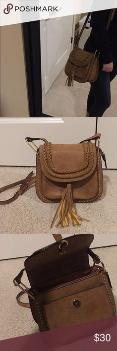 brown braided crossbody like new adorable crossbody bag ! braids, gold studs and fringe details cover the front. gold detailing & a adjustable crossbody strap. two pockets on the inside; one zipper & one not, as well as a pouch in the front under the button clasp. it's a must for any season ! feel free to make me an offer (: Bags Crossbody Bags