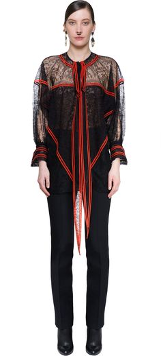 A beautiful lace, for this woman's shirt in black with red profiles in contrast. Stripes on a romantic and seductive lace. Shirt with buttons on the front and some laces, you could slid it over your shoulder. Cuffs also with red stripes are a little bit wide. Shirt very fine from Givenchy, synonymous of beauty and elegance.