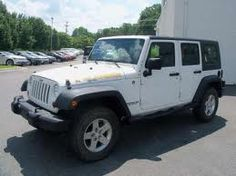 Four door white Jeep Wrangler with black hard top  Need some different wheels.