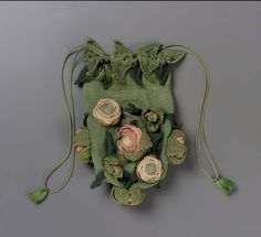 "1820-1860, Europe - Drawstring bag - ""Rose Bud"" drawstring bag. Green silk knit with appliquéd pink, salmon, ecru roses and yellow-green, green, dark green leaves. Green cord drawstring."