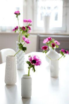 Purple flowers in white vases