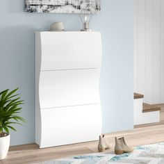 With room to store 24 pairs of shoes, this large shoe cabinet is a highly functional choice for the home. It has a vertical orientation with a high-gloss finish and a wave-like design, so it matches well with contemporary interiors. Assembly is required.