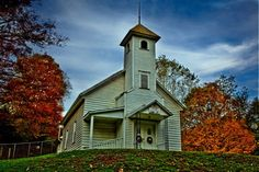A small country church found in the mountains of West Virginia. On a clear autumn day the fall colors around this church accent the old fashioned charm of a little white church beside the road.