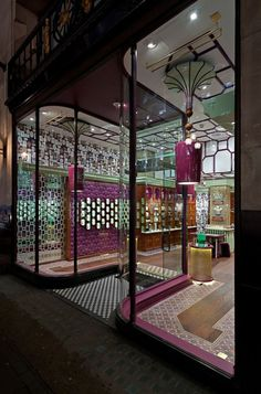 Giant padded walls, punctured by sticky chamfered light boxes, draw the eye into a kaleidoscope of heritage; ceiling roses inspired by Westminster Abbey introduce a Tudor fretwork ceiling from which glossy Brighton Pavilion Onion Dome chandeliers are suspended.