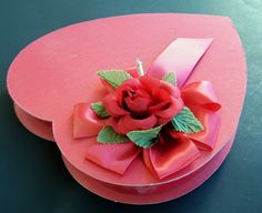 1992 Russell Stover Valentines Chocolate Heart Shaped box , red satin box with lovely silk rose corsage on a red satin bow.     It is a lovely box,