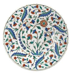A polychrome Iznik pottery dish, Turkey, second half 16th century, of shallow round form, decorated in underglaze cobalt blue, green and relief red with black outlines, floral sprays including carnations and hyacinths, the rim with a pattern of overlapping saz leaves and floral stems.: