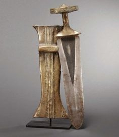 Couteau et fourreau Konda R.D. Congo Fer forgé, bois et feuille de laiton H_48 cm Les Konda sont un peuple Mongo renommé pour ses armes. La qualité de la lame est égalée par l'apparat du fourreau gainé de laiton.