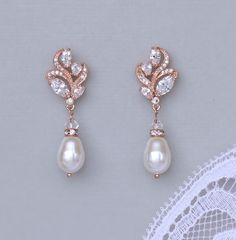 Rose Gold Bridal earrings made with Swarovski crystals are set in a graceful leaf shaped design for a classic and delicate earring. A Swarovski pearl teardrop in your color choice creates the perfect accessory for your wedding. We have used ivory white pearls in the photos. Choose your colors from the drop menu.  These earrings have such a lovely sparkle and would make a beautiful Bridesmaids accessory.   Available in rose gold, silver (rhodium) and gold Measurements: Length - 1.25 Width…