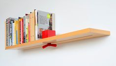 The Hold on Tight bookshelf features an integrated bookend that can be moved to accommodate different numbers of books. The bookshelf is a concept by Brook
