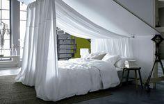 Bed opgemaakt met wit beddengoed staat onder een schuin plafond; met stof die aan het plafond hangt is een bedhemel gemaakt