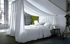 A bed with white linens sits under a sloped ceiling, and white textile hangs from the ceiling to create a canopy.