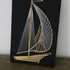 This tiny string art is constructed on black felt mounted on a wooden plaque. The boat is completed in gold metallic string, sails are a combination of