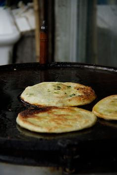 Cōng Yóu Bǐng 蔥油餅 fantastic snack at any time of day.These crispy layered pancakes are made from unleavened dough and speckled through with green onions and sometimes little cubes of salt pork, then pan fried and served hot. Crisp and crunchy on the outside, with warm flaky dough in the middle, a little like a paratha, a lot like the best hot, salty snack you can taste for under 30 cents.
