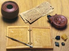 Roman writing equipment from Verulamium (St Albans). Only the lamp, wax tablet & wafer thin wood tablets are modern replicas. The ink pot, stylus, seal box and signet ring are original finds.