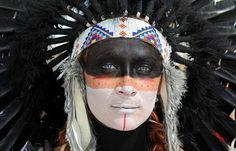 Katrina Van-Marter of Texas wears makeup and a feather headdress at the Burning Man festival