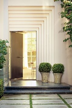 tiered entry way with off center pots with boxwood