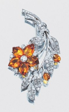 Cabochon Citrine and Diamond Flower Brooch   Platinum, the stylized floral bouquet accented by 7 marquise-shaped and pear-shaped cabochon citrine petals, one flower highlighted by 6 round diamonds, the delicately pierced leaves set with numerous single-cut diamonds, # N8750, circa 1950, approximately 9.7 dwt.