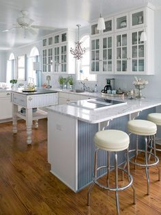 Beautiful white kitchen with white carera marble, blue bead board, white leather barstools, white kitchen island with black slate top, and white glass door cabinets.