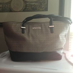 "Kenneth Cole Duplicator Saffiano Tote - Gray color This Kenneth Cole Duplicator Saffiano Tote includes a faux leather exterior, gold-tone hardware, a front snap closure, and dual handles with a drop of 10 inches. The interior includes a classic lining, 2 slip pockets, and 1 zipper pocket. Dimensions: 10""H x 17""W x 6""D. Kenneth Cole Reaction Bags Totes"